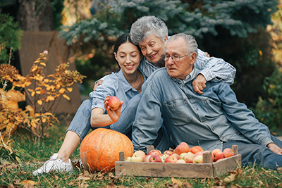 Family Sitting In A Garden With Apples And Pumpkin